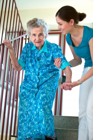 care at home: Senior woman is climbing stairs with caregiver