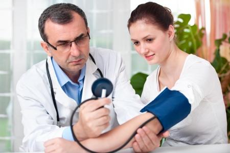 sick person: M�dico hombre controla la presi�n arterial joven mujer