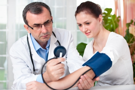blood pressure gauge: Male doctor checking young woman blood pressure