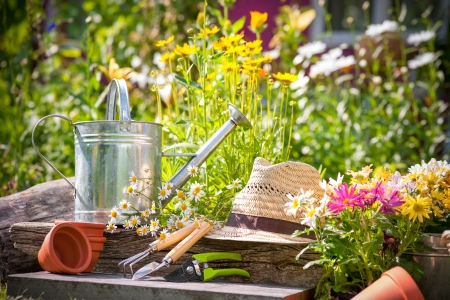 Gardening tools and a straw hat on the grass in the garden Archivio Fotografico