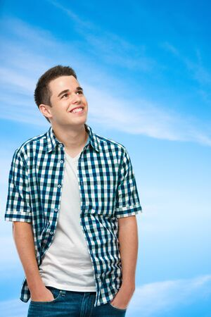 Student teenager dreaming about something on blue sky background photo