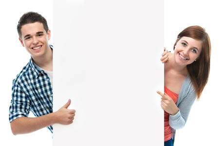 two smiling teenagers holding at a blank board photo