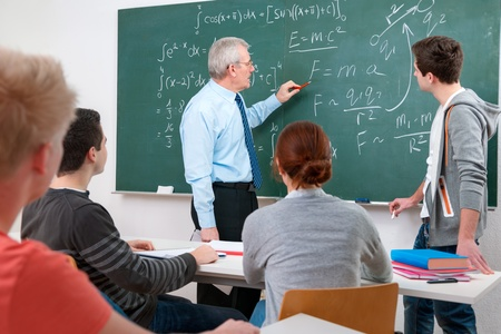 teacher training: Teacher with a group of high school students in classroom Stock Photo