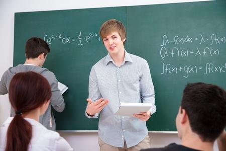 estudiantes de secundaria: Los estudiantes de secundaria en discusiones tarea delante de la pizarra