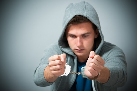 Arrested teenager with handcuffs on his hands Stock Photo