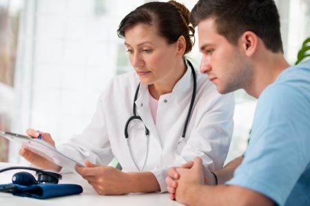 checkup: doctor talking to her male patient at office