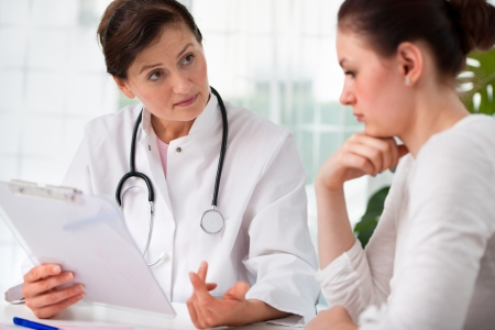 doctor examining woman: doctor explaining diagnosis to her female patient Stock Photo