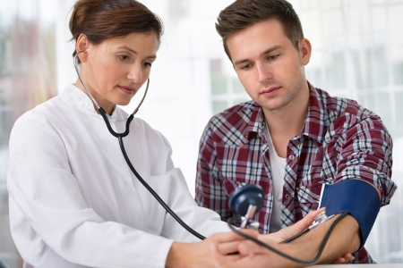 medics: Female doctor checking young man blood pressure