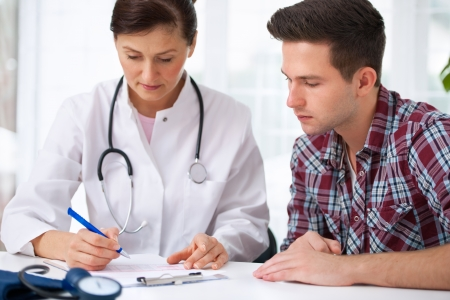 patient and doctor: doctor talking to her male patient at office