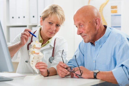 physical therapist: Physical therapist talking to patient and explains the cause of his pain Stock Photo