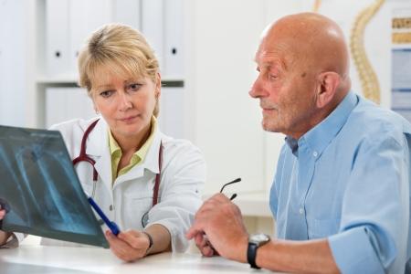 canc�rologie: Docteur en expliquant x-ray r�sultats patient �g�