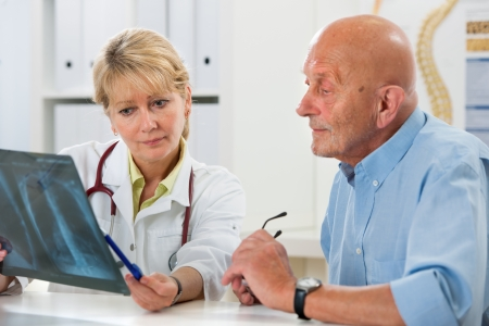 polmone: Medico che spiega raggi X i risultati al paziente anziano