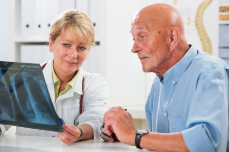 lung cancer: Doctor explaining x-ray results to senior patient Stock Photo