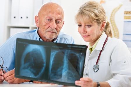 paciente: M�dico explicando los resultados de la radiograf�a con el paciente mayor Foto de archivo