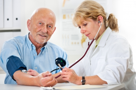 blood pressure gauge: Female doctor measuring blood pressure of senior  man Stock Photo