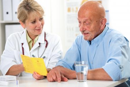 medico con paciente: Hombre mayor que recibe un certificado internacional de vacunaci�n del m�dico