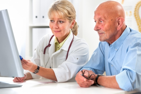 doctor computer: doctor talking to her male senior patient at office