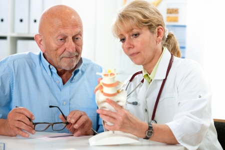 physical exam: Physical therapist talking to patient and explains the cause of his pain Stock Photo