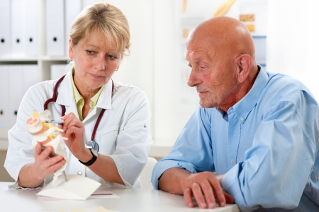 spinal adjustment: Physical therapist talking to patient and explains the cause of his pain Stock Photo