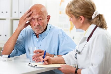 dolor de cabeza: Paciente le dice al m�dico acerca de sus quejas de salud Foto de archivo