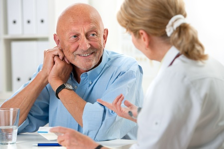 hospital patient: doctor talking to her male senior patient at office