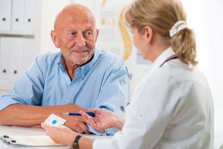 elderly pain: medico parlando con il suo paziente di sesso maschile senior ufficio