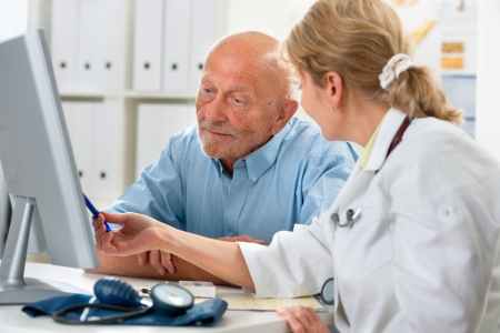 patient and doctor: doctor talking to her male senior patient at office