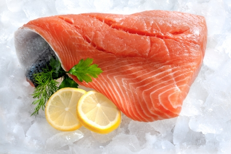 frozen fish: fresh salmon fillet with parsley and lemon slices on ice