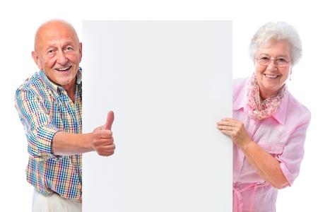 Glücklich lächelnde ältere Paare, die eine leere Bord isoliert auf weiß Standard-Bild - 15785951