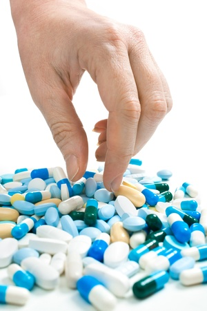 hand taking pills from the heap of different medications photo