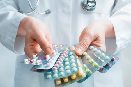 medical decisions: Hand of doctors holding many different pills Stock Photo