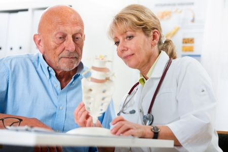 physical test: Physical therapist talking to patient and explains the cause of his pain Stock Photo