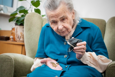 pensioner: elderly caucasian woman counting coins in her hands