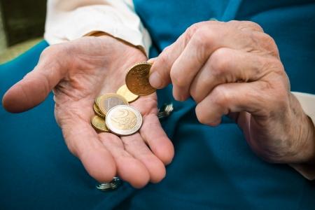 monete antiche: Anziani caucasica donna contando i soldi in mano Archivio Fotografico