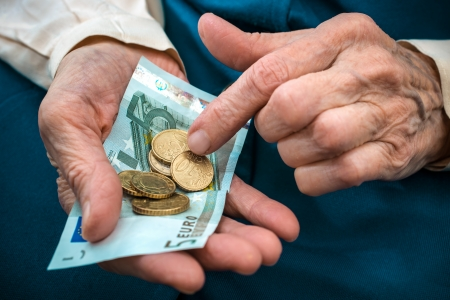 pensions: elderly caucasian woman counting money in her hands