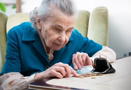 coin purse: elderly caucasian woman counting money  on table