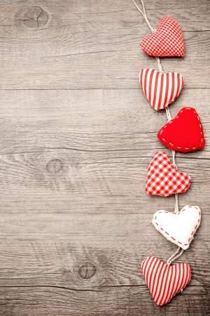 Red hearts hanging over grey wood background photo