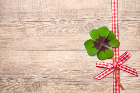 Four leaf clover and red ribbon over wooden background photo