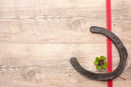 horseshoes with  four leaf clover over wooden background Stock Photo - 17475008