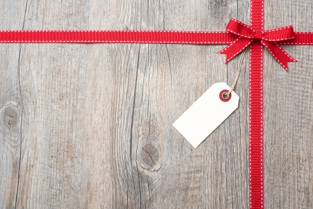 red x: Red ribbon and bow with address label attached over wooden background