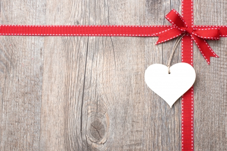 Red ribbon and bow with heart  over wooden background Stock Photo