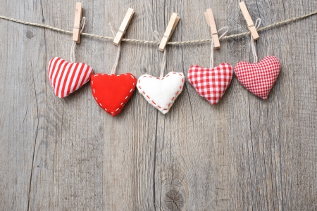rustic christmas: Red hearts hanging over grey wood background