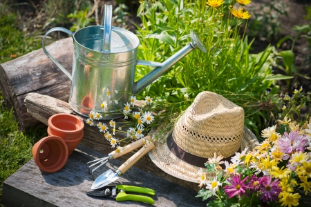 gardening tools: Gardening tools and a straw hat on the grass in the garden Stock Photo