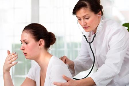 tos: doctora examina a un hombre joven resfriados Foto de archivo