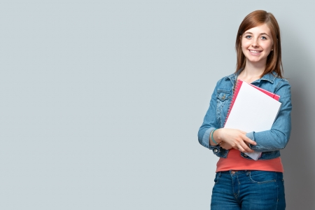 highschool students: smiling teenage girl standing with books against the wall