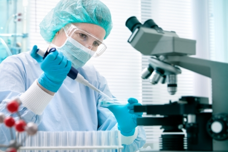 investigador cientifico: Cient�fico con cuentagotas a trabajar en el laboratorio Foto de archivo