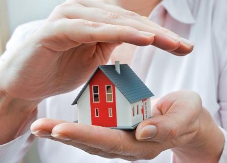 agente comercial: Manos que presentan un pequeño modelo de una casa Foto de archivo