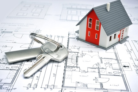 mortgage: model of a house and key ring on a blueprint