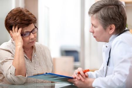 환자: 여성 환자는 그녀의 건강 불만 사항에 대한 의사를 알려줍니다 스톡 사진