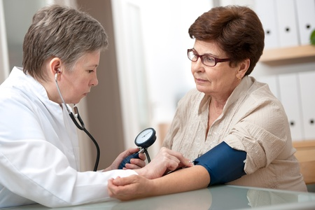 blood pressure gauge: doctor measuring blood pressure of female patient